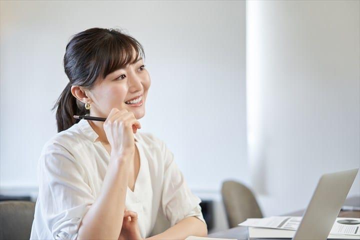 笑顔で考える女性、ノートパソコン