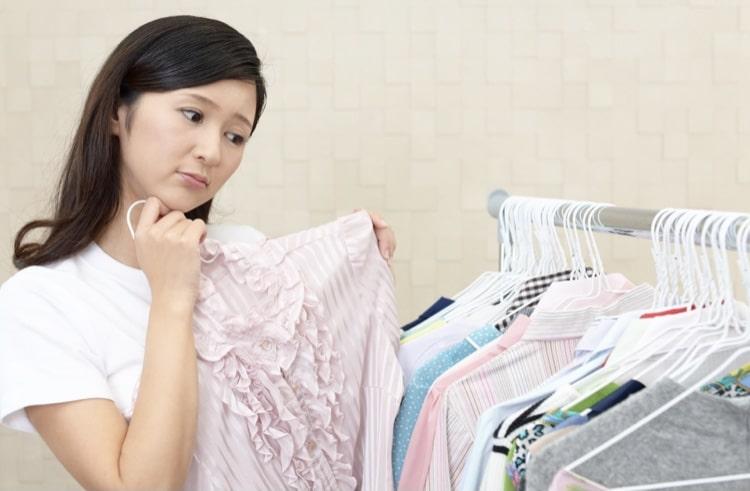 服を見ながら悩む女性