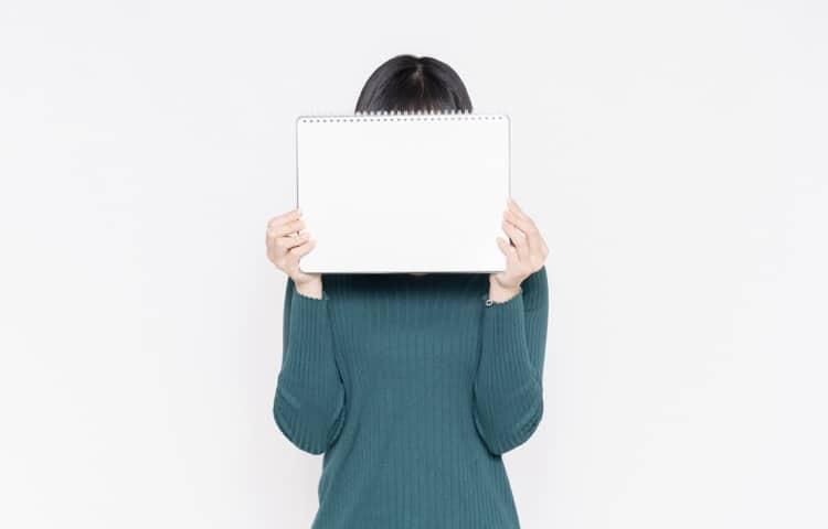 スケッチブックで顔を覆う女性