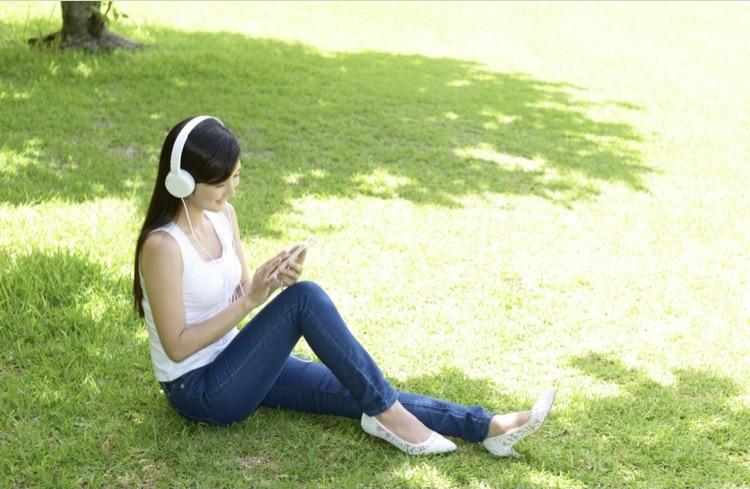 木陰で音楽を聴く女性