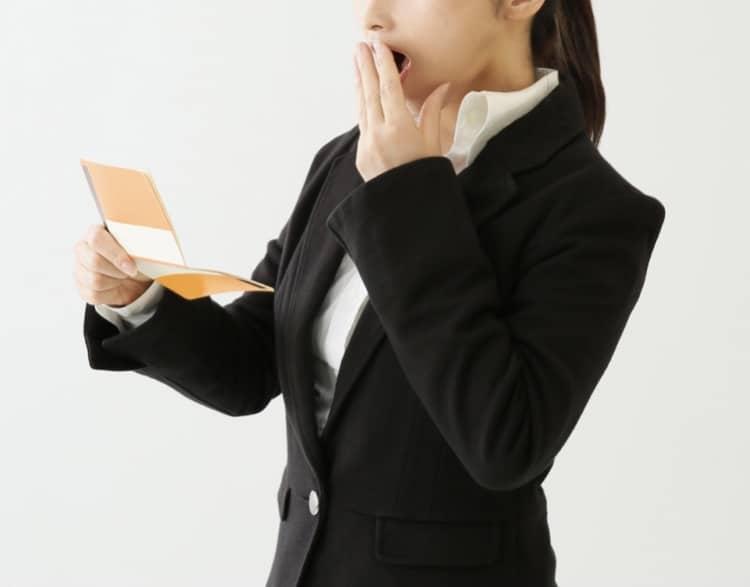 通帳を見て驚く女性