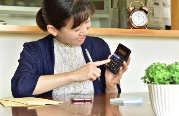 電卓を手に持つ女性