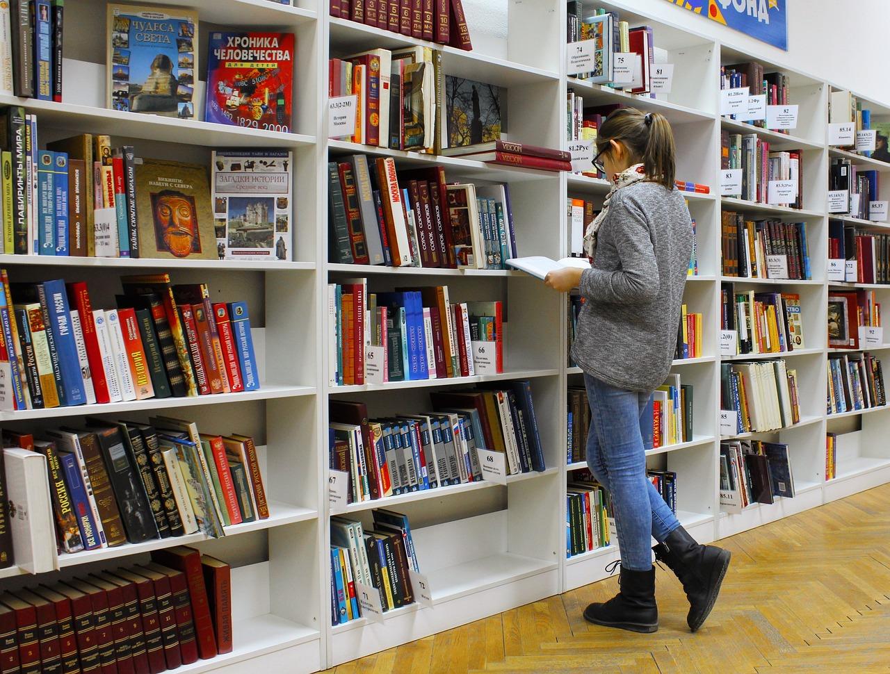 本を探す女性の画像