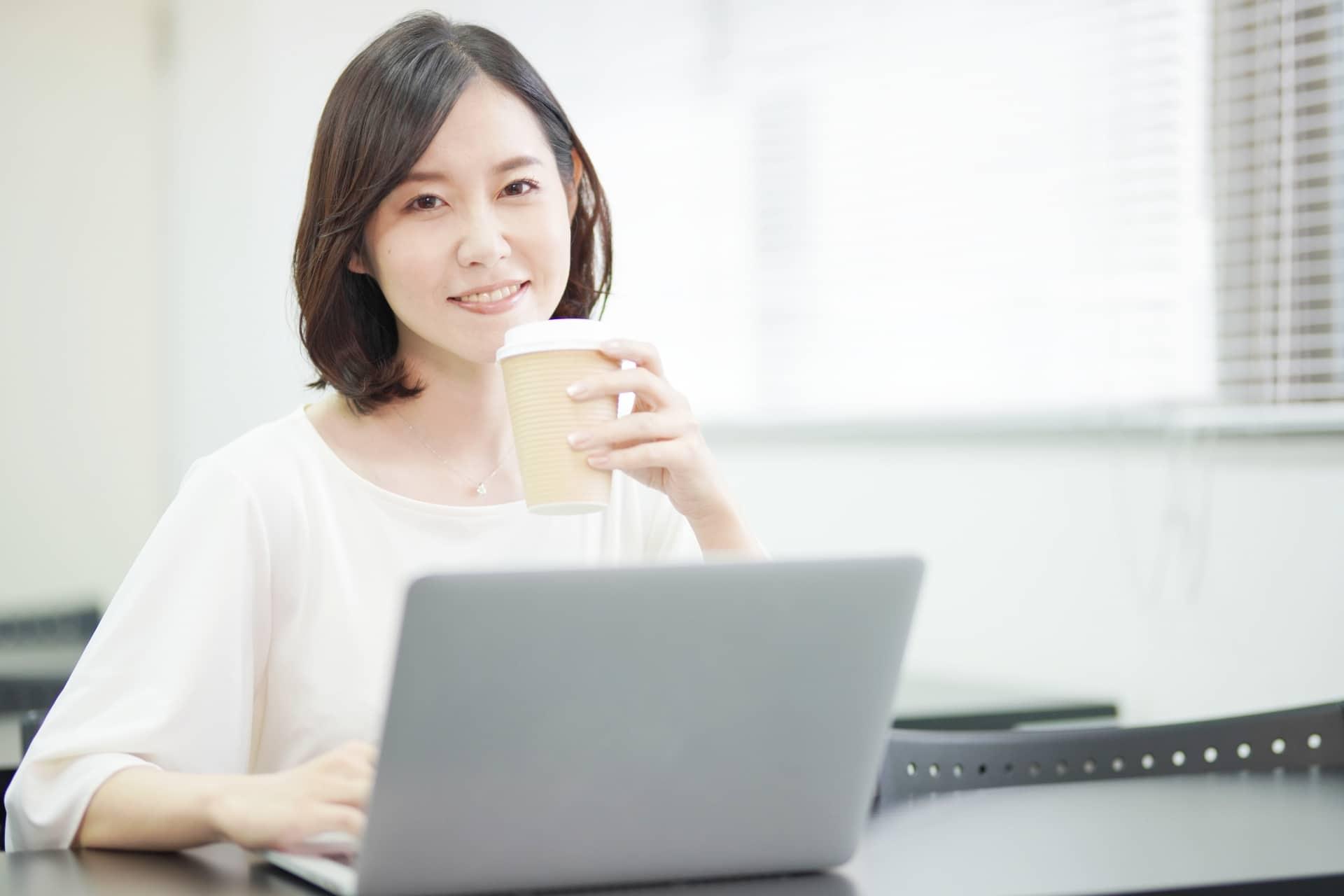 パソコンの前でコーヒーを飲む女性