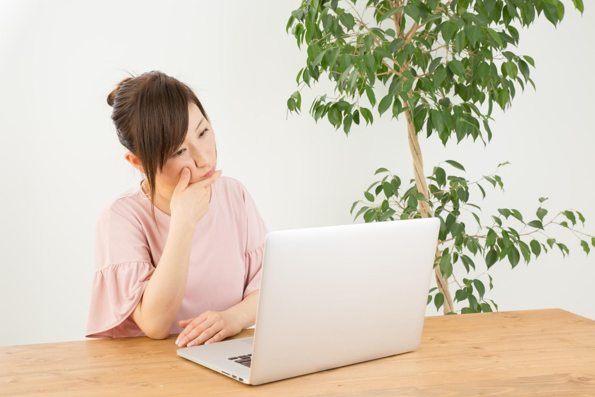 ノートパソコンを見て考える女性