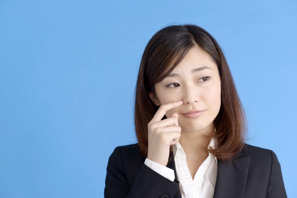 鼻をかく女性