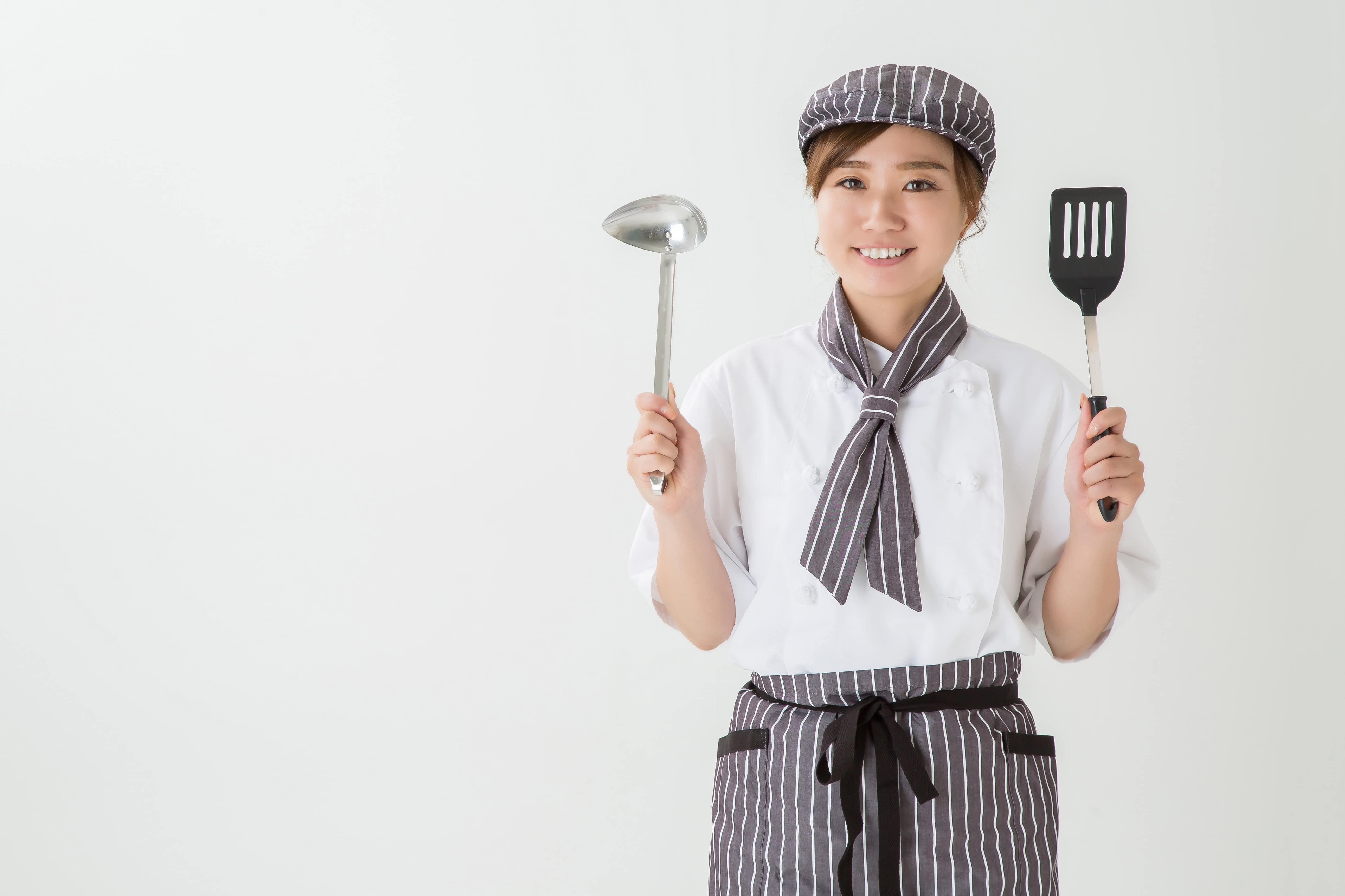 キッチンツールを持つ女性