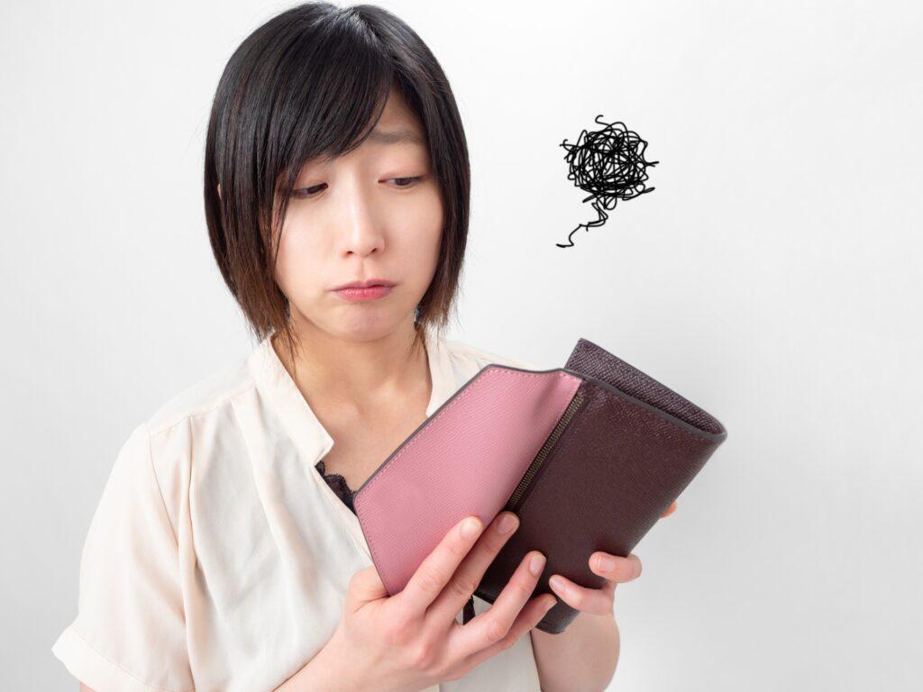 財布を見て不安になる女性