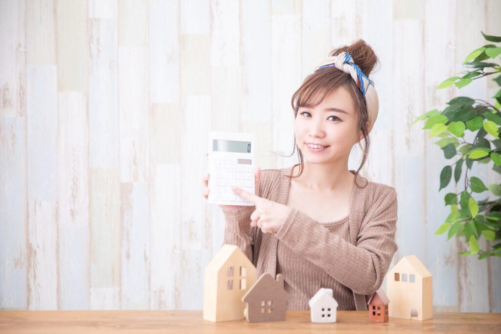 電卓をもつ女性と住宅の模型