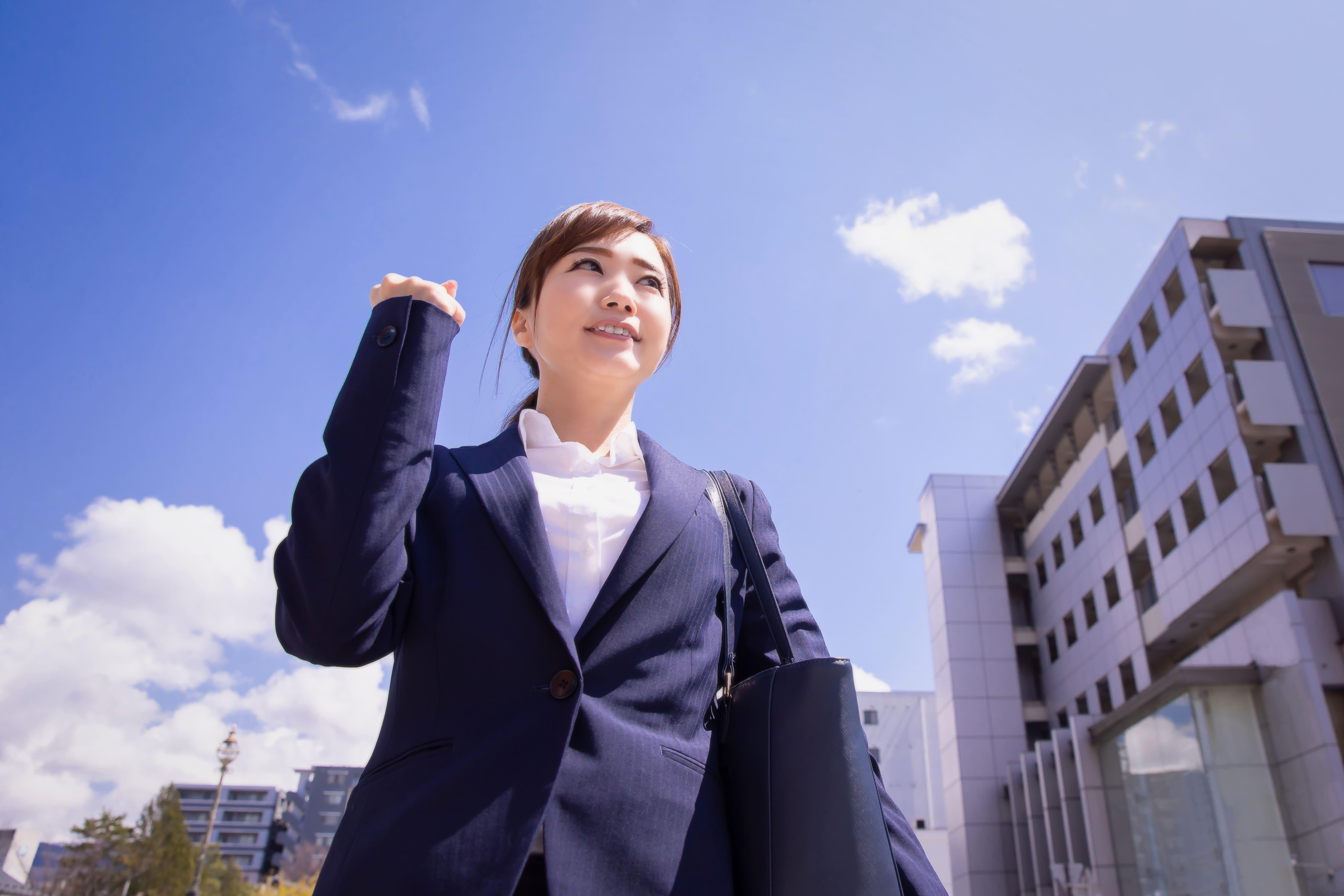 空とスーツ姿の女性