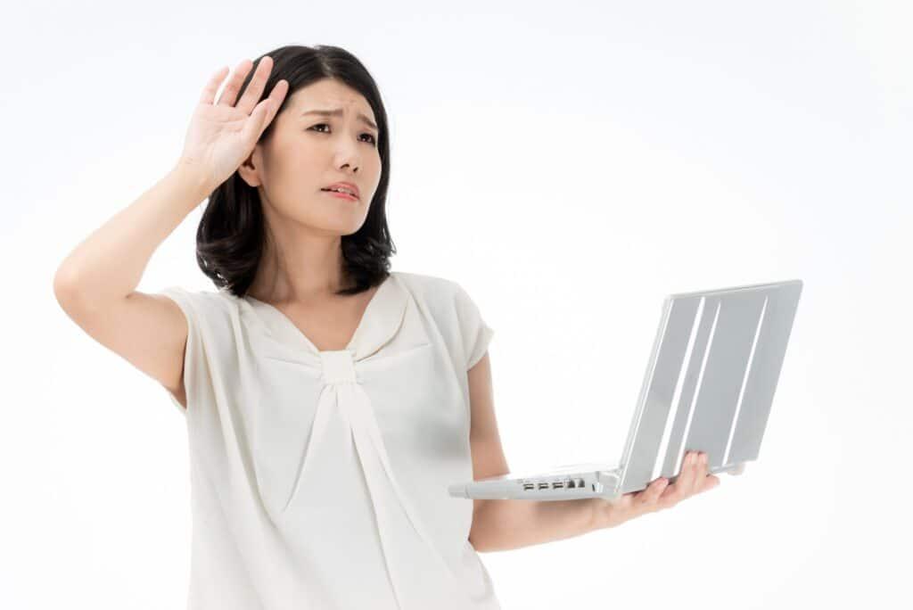パソコンを持って悩む女性