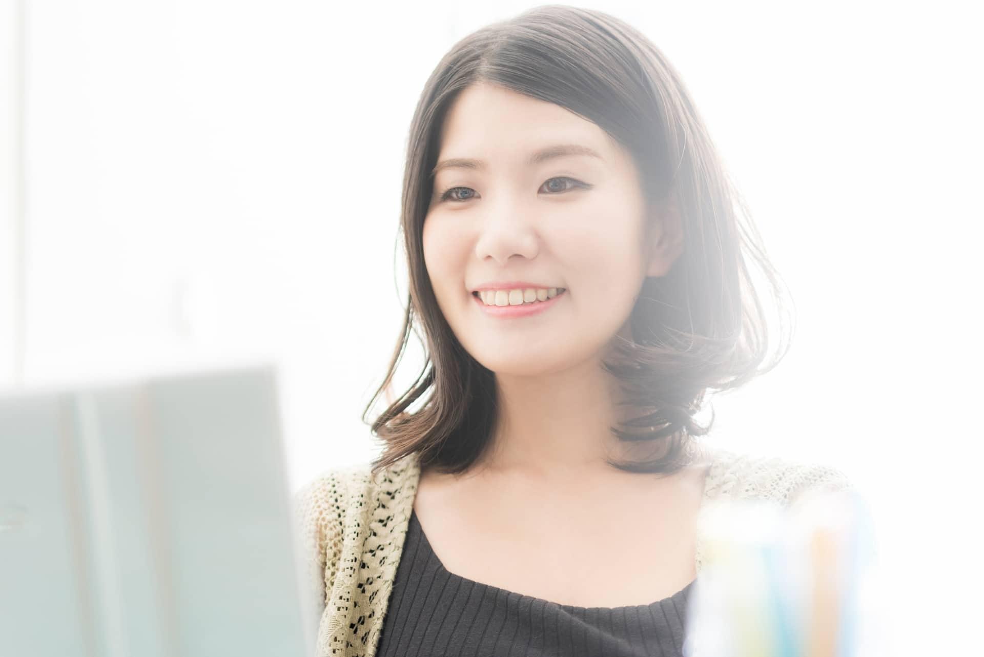 パソコンをしながら微笑む女性