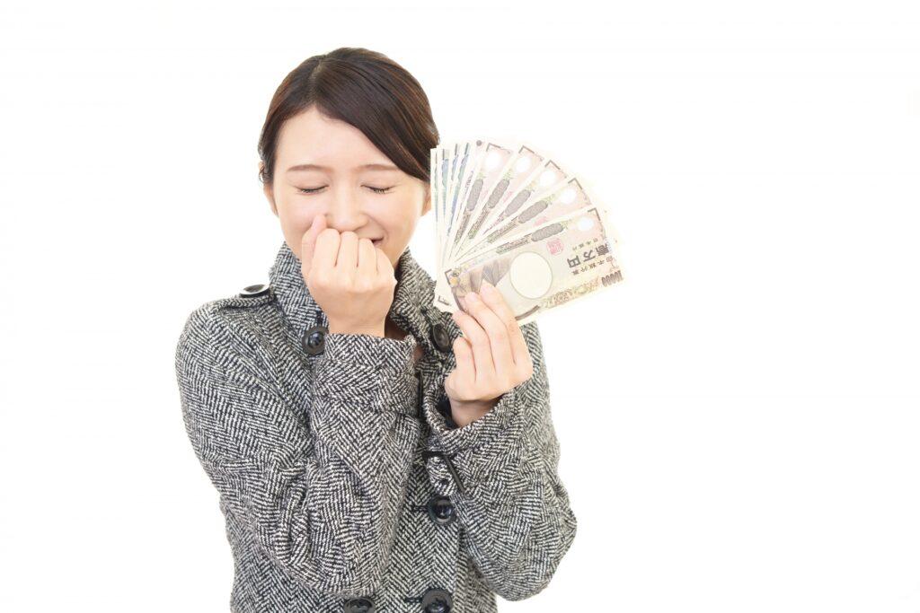 お金を持って微笑む女性