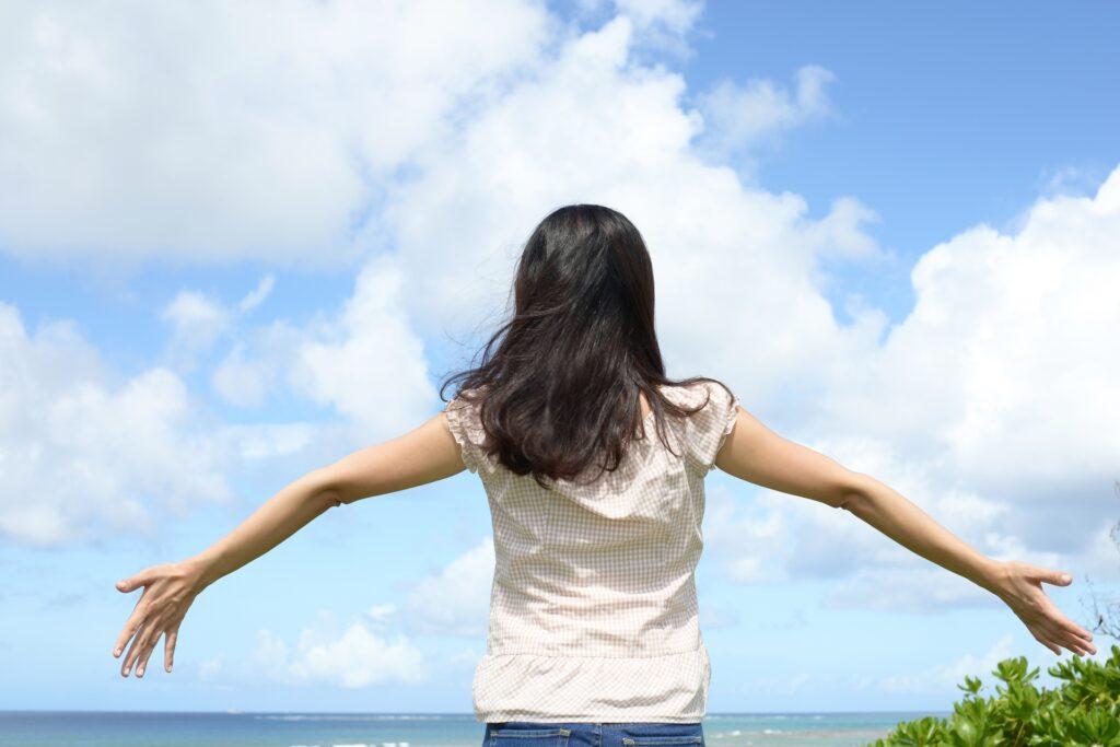 両手を広げる女性の後ろ姿、海辺