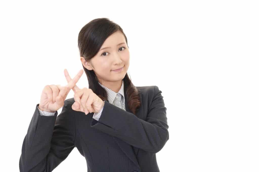指でバツを出す女性