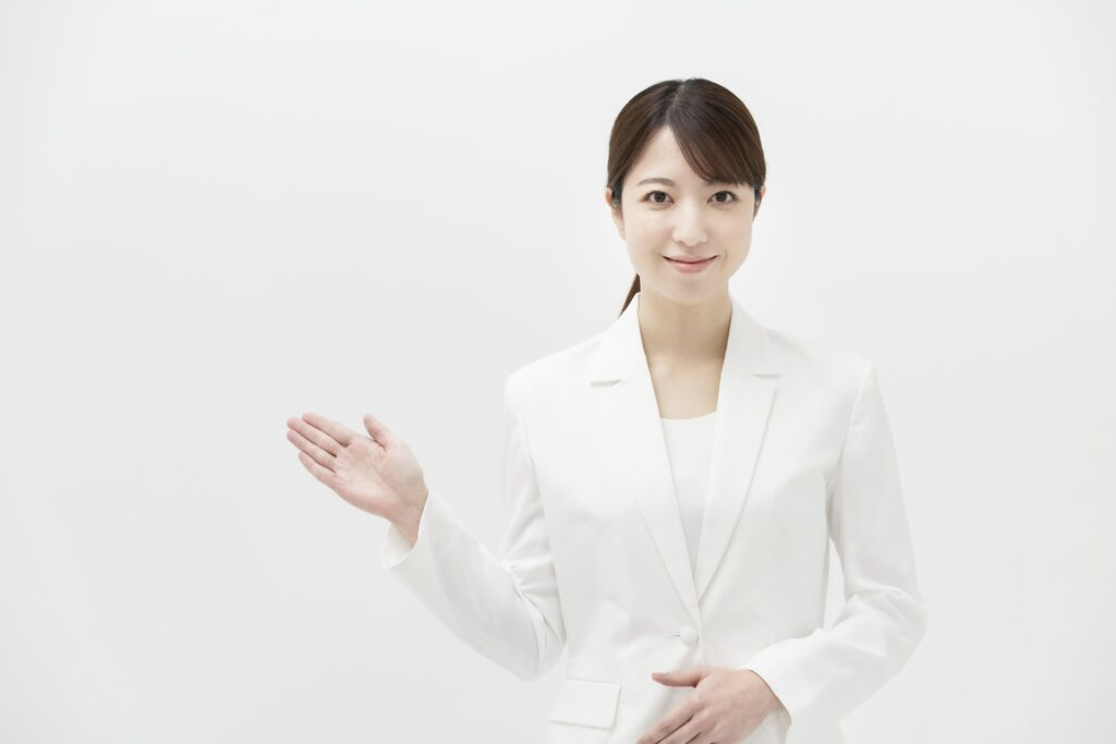 案内をする白いスーツを着た女性