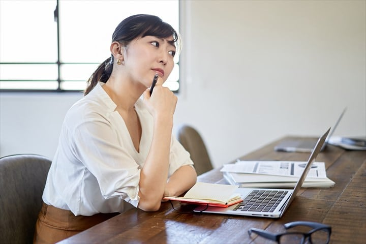 ノートパソコン、考える女性