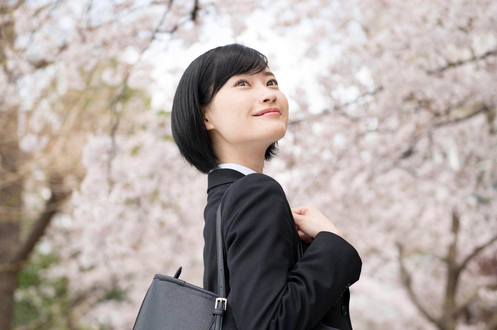 桜と就活生の女性