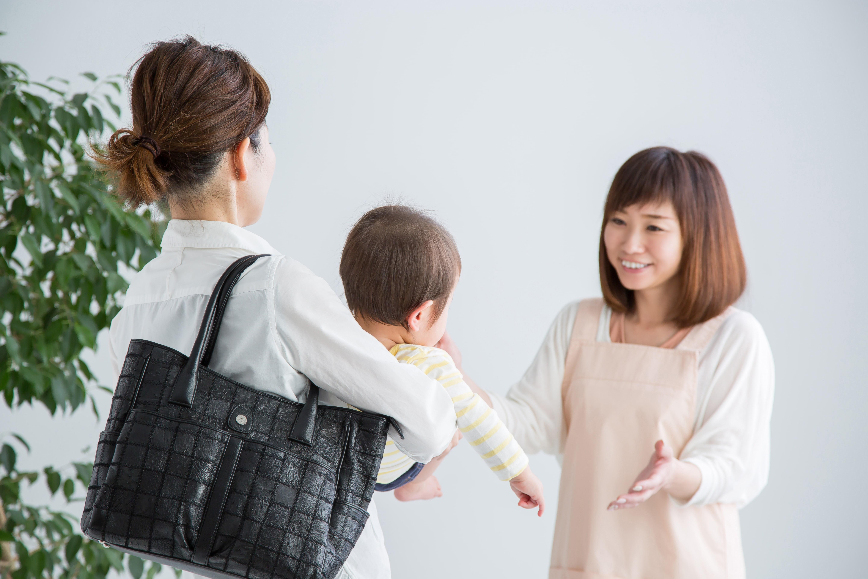 保育園に子供を預ける女性