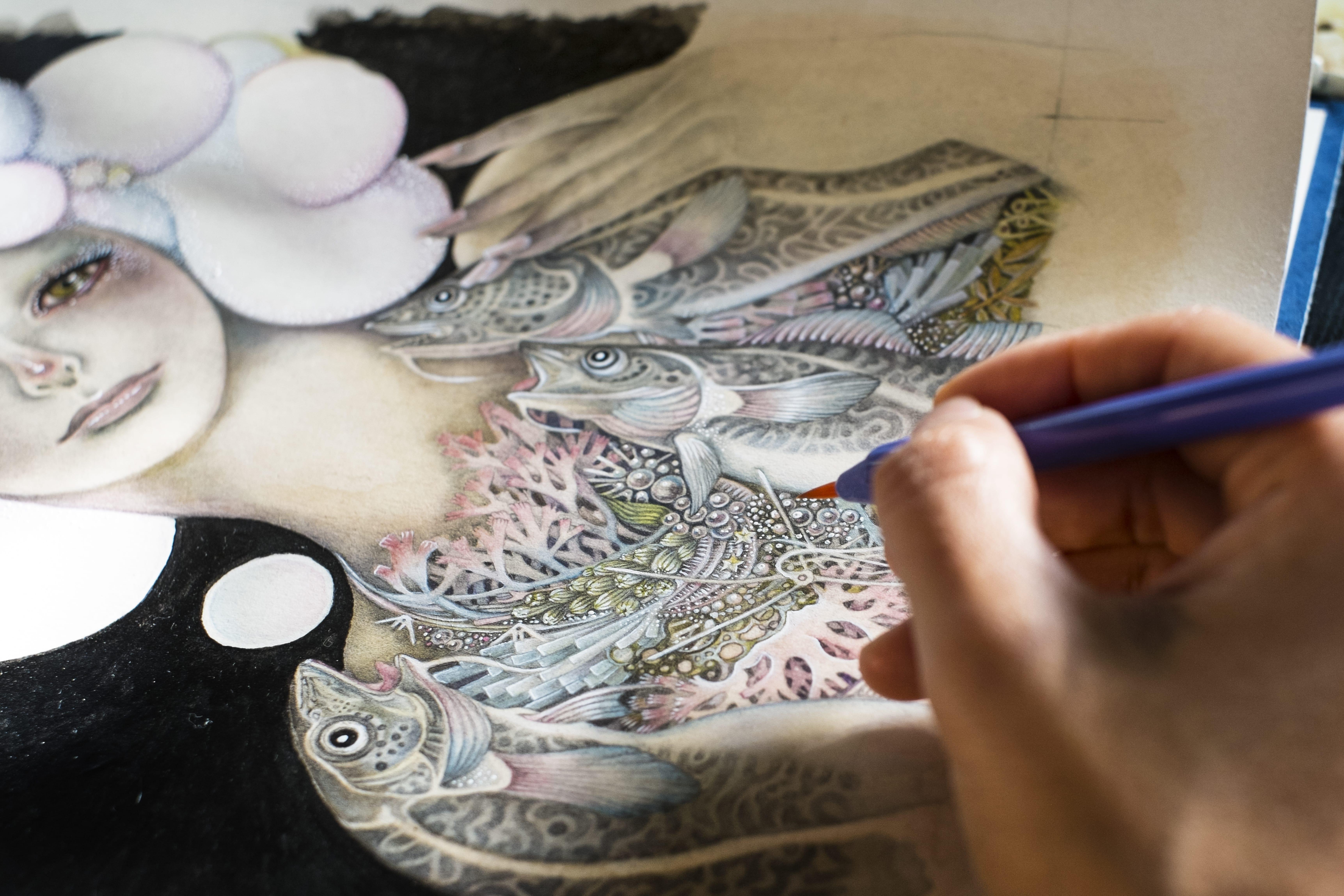 緻密な絵を描く女性の手元