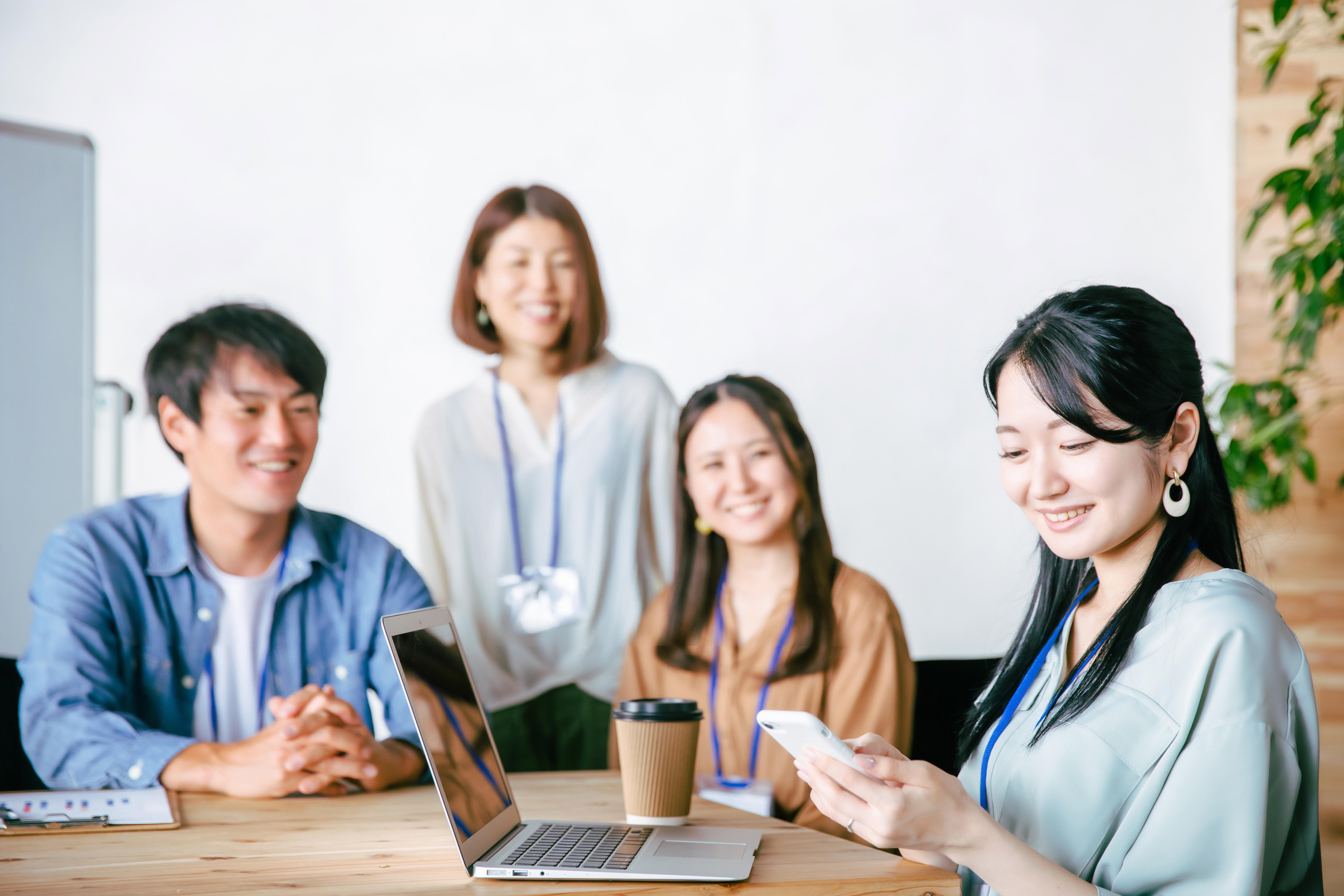 スマホを使う会議中の女性