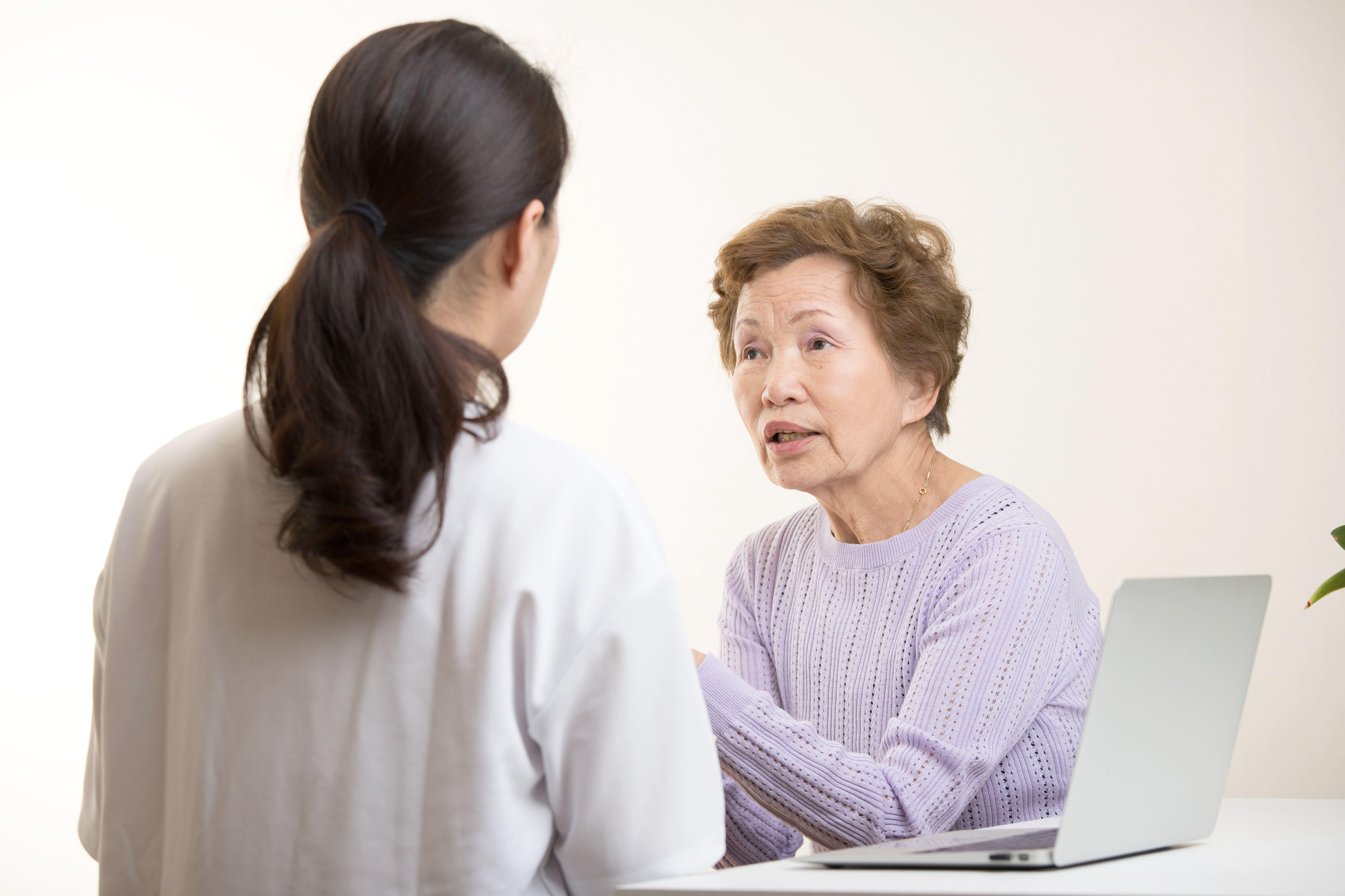 高齢者の話を聞く女性